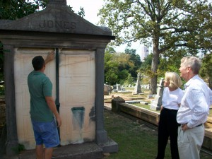 ... but the doors on the Jones Mausoleum may fall apart and a metal clamp along the base of the roof holds the walls together, as Dustin Hornsby shows Libba Grace and David Moore.  Credit: David Pendered