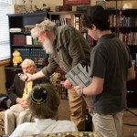 Photo of filmmaker Jacob Rhodes checks the lighting as Grady High School students Eli Mansbach (standing) and Jack Arnold prepare to interview Holocaust survivor Herbert Kohn as part of the Congregation Shearith Israel Teen Film Project.