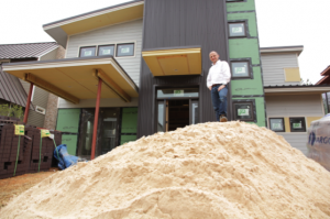 Luis Imery stands in front of net-zero home under construction in Serenbe