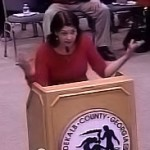 Photo of Heidi Pollyea, wearing red as she speaks to the DeKalb County Board of Commissioners. (Credit DeKalb County/DCTV)