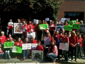 Photo of The shelter supporters show up at every Board of Commissioners meeting, wearing red and standing whenever one of their group speaks to the board members.