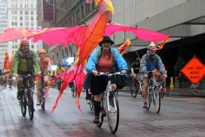 Atlantan Chantelle Ryttter rides down Peachtree with a phoenix attached to the back of her bicycle (Photo: Cameron Adams)