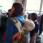 Photo of clothes shopper at clothes swap with baby on her back.