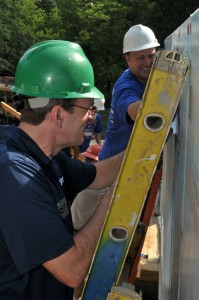 Habitat's Jonathan Reckford  and Newell Rubbermaid's Michael Polk work together installing a window at a home under construction