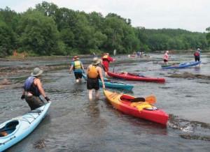 Paddlers walk their vessels over shoals on the Flint River in 2008. Credit: Joe Cook via Flint Riverkeeper