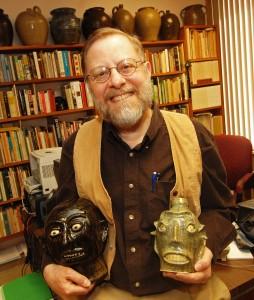 Folklorist John Burrison holds two face jugs from his collection. Photo by Carolyn Richardson