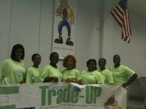The first all-female pre-apprenticeship program offered by Georgia Trade-Up stand beneath a sign of an iconic tradesman: Tyeshia Foster (left to right); Lisa Brooks; Jacquelyn Treadville-Sanders (president); Leslee Shepherd (coordinator); Janell Carter; Joanne Barker; Chamena Johnson (secretary). Photo credits: David Pendered