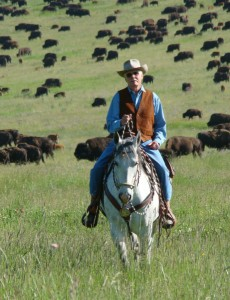 Ted Turner on horseback, riding through a bison herd in Montana (Photo by Elena Cizmaric)