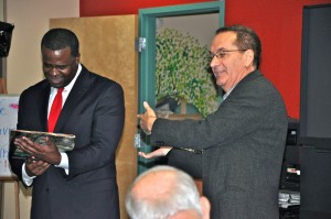Mayor Kasim Reed accepts a gift from Mike Koblentz, chairperson of the Northwest Community Alliance. The gift was a Life magazine featuring President John Fitzgerald Kennedy. Credit: Donita Pendered