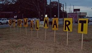 Photo of sign protesting Walmart at Suburban Plaza.