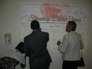 Members sign their memories on a poster in the Fellowship Hall