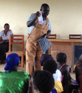 Photo of George Ovola, who works with Aid Africa, teaches girls in Uganda how to use feminine hygiene supplies sewn by Atlanta volunteers with Days for Girls International. (Credit: Melissa Moody)