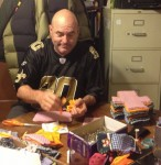 While watching football, Cassie Catalanotto's husband Carl sorts shield pockets that are used for feminine hygiene kits for needy girls. Cassie is the Days for Girls director in New Orleans. (Photo from Melissa Moody)