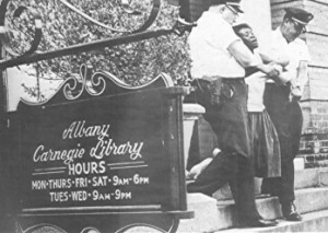 A woman is arrested for violating Jim Crow laws at the segregated Albany Carnegie Library.
