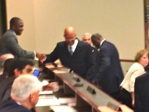 "The image is fuzzy, but the handshake is of note as DeKalb County Interim CEO Lee May congratulates newly installed ARC board member Minuard ""Mickey"" McGuire. Credit: David Pendered"