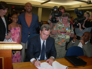MARTA Chairman Robbie Ashe signs the Clayton resolution as others look on