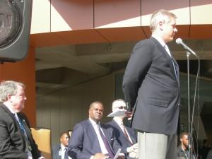 On the podium (left to right): Steve Hatchell; Mayor Kasim Reed; Steve Robinson and John Stephenson Jr. (standing)