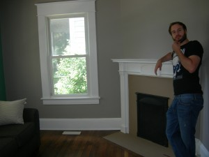 David stands next to the fireplace in the front room