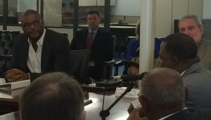 Tyler Perry listens to Mayor Kasim Reed at MILRA board meeting