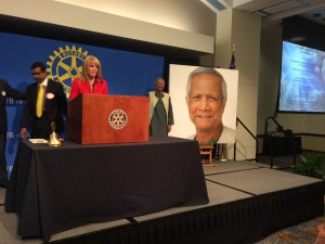 Muhammad Yunus stands next to his portrait at Rotary meeting after unveiling