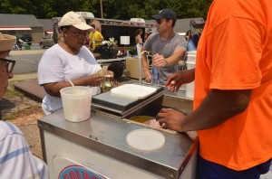 Atlanta Councilwoman Natalyn Archibong buys a cold treat from Dolphins Water Ice, a Kirkwood-based business, at the grand opening of the East Atlanta Corner Project. Archibong's mother, Gwendolyn Mosby, is  visible on the left side of the photo. Credit: Sylvia McAfee