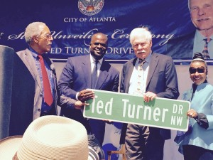 Ted Turner and Atlanta Mayor Kasim Reed hold new street sign as others look on