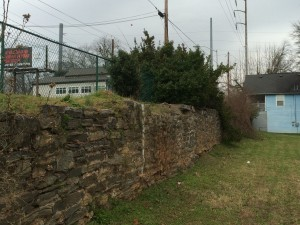 This stone retaining wall is adjacent to Joseph E. Boone Boulevard. Atlanta intends to create a pond south of the wall to retain storm water. The blue dwelling is to be demolished. Credit: David Pendered