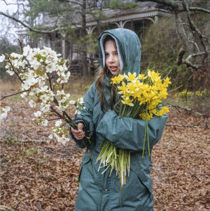 A girl picks an armful of heirloom daffodils from the historic landscape of an abandoned Georgia homesite. Photo by Anderson Scott