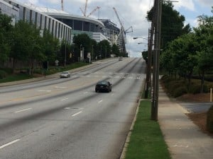Looking south along Northside Drive, toward the Mercedes-Benz Stadium, shows a five-lane road with a dedicated turn lane, with few places to turn into, and two sidewalks. Credit: David Pendered