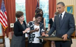 Georgia artist Lois Curtis (center) presents President Obama with a painting to commemorate the 12th anniversary, in 2011 of the Supreme Court's Olmstead decision. Curtis was one of two women who sued to be released from a state psychiatric hospital after the state determined she could live in a small group home. Credit: whitehouse.gov