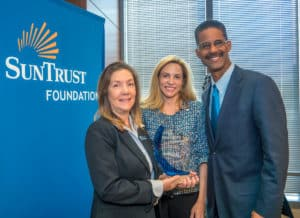 The SunTrust Foundation presented Atlanta-based Project Community Connections, Inc. with its inaugural Lighting the Way Award. The award comes with a $50,000 and recognizes non-profit organizations for their support of sustainable financial well-being initiatives. PCCI was selected for the positive impact their rapid re-housing program has had in helping homeless individuals and families reestablish themselves in the community and find a place to call home. The ceremony included Margaret Schuelke (left), PCCI's executive director; Allison Dukes, president and CEO of SunTrust Bank's Atlanta division; and Samuel Bacote, PCCI's chairman. Credit: SunTrust Foundation
