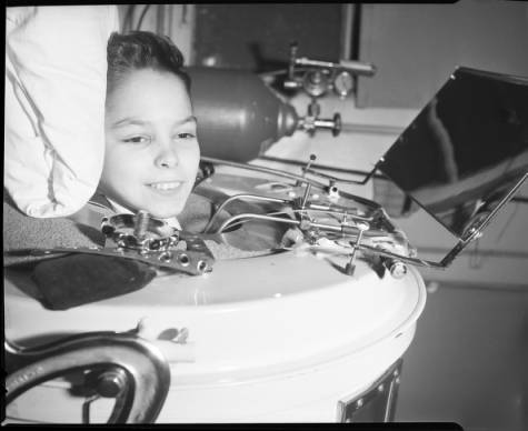 A child demonstrates the use of an iron lung. Courtesy of the Atlanta Journal-Constitution and Georgia State University