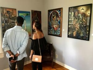 Visitors browse the Wolf Idea Group's gallery at Fort McPherson at an opening event on July 8. Credit: Kelly Jordan