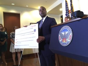 Atlanta Mayor Kasim Reed, pictured in his City Hall office on Thursday, presented a poster listing fines City Council President Ceasar Mitchell injured for failure in an earlier campaign to disclose campaign spending, campaign debt and for late filing of personal financial disclosures.