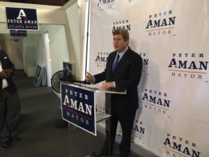 Atlanta mayoral candidate Peter Aman, speaking at his campaign headquarters on Wednesday, called for an end to City Council staff moonlighting on their bosses' election campaigns. Credit: Maggie Lee