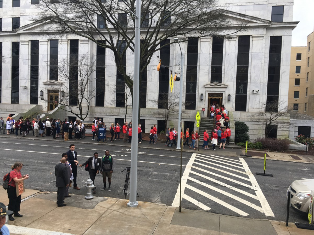 Folks in red wait in the outdoor half of a line to go through metal detectors and visit the state office building across from the Capitol. Credit: Maggie Lee