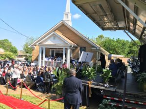 Bishop Dexter L. Johnson addresses a crowd outside of his Higher Ground Empowerment Church, at a ceremony for the groundbreaking of a new senior apartment complex. The church is a partner in building it. Credit: Maggie Lee
