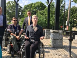 Laurel Lawson, speaking at Vine City Park on June 11, 2018, said that broken and impassible city sidewalks have forced her to roll on the street. Credit: Maggie Lee