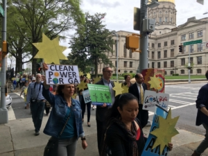 Folks demanding cleaner, more affordable energy marched past the state Capitol en route to a short demonstration at the next-door Public Service Commission on April 8. Credit: Maggie Lee
