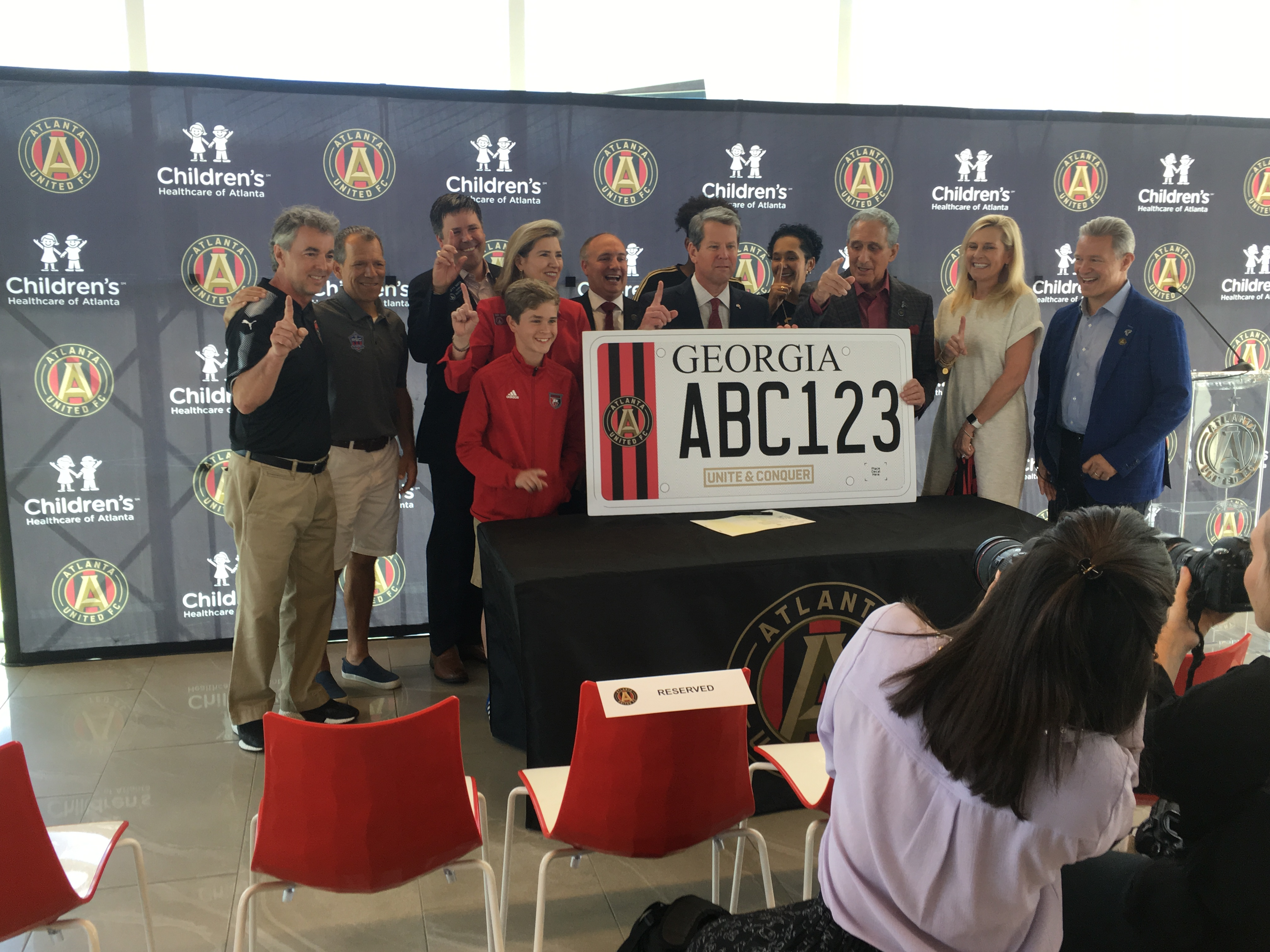 Gov. Brian Kemp (center front) plus Atlanta United management and other fans at the bill-signing on May 6. Credit: Maggie Lee