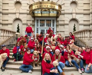 Dogs and people sitting on hotel steps, many wearing red and Santa hats