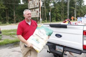 A man carrying a bag of pet food.