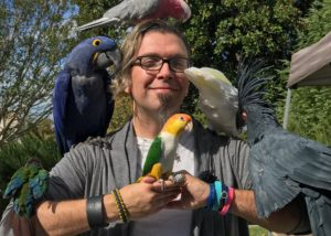 A man with several birds sitting on him