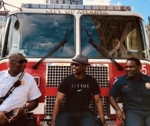 Firefighters leaning on the front of a fire truck