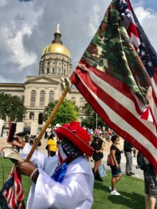A person carries a U.S. flag in front of the Georgia Capitol