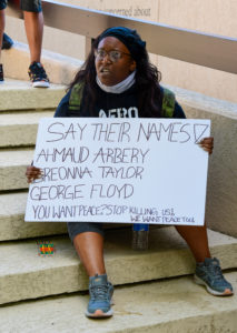 """Protestor with """"say their names"""" sign"""