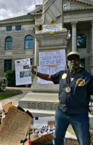 A man in front of the obelisk, which is covered in signs.