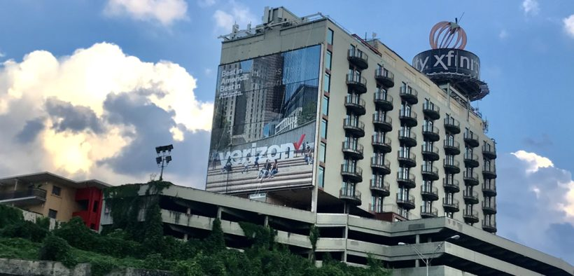 1655 Peachtree street, a buiding with a large billboard on the side and a round billboard on top.