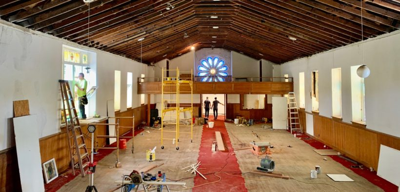 Renovation workers, scaffolding, construction tools inside church