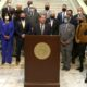 A bipartisan group of lawmakers stand with Republican Gov. Brian Kemp Tuesday as he announced plans to curtail Georgia's citizen's arrest law. (Credit: screenshot)